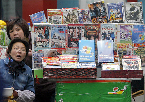 Vendors have their lunch at a stall selling pirated DVDs and software in Nanjing.