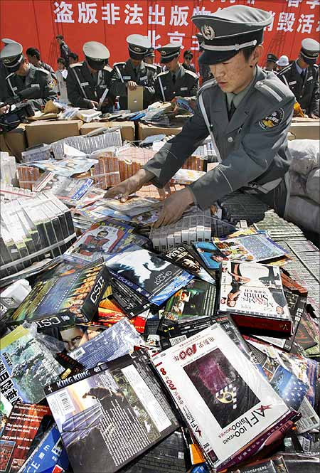Chinese security officers prepare to destroy pirated DVDs and software during a ceremony in Beijing.