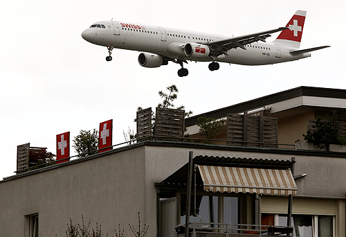 An Airbus A321-111 of Swiss International Air Lines is seen behind an apartment building during its approach for a landing at Zurich Airport.