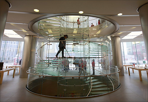 A cleaner mops a stairway at an Apple store during the release of iPhone 5 in Beijing's Wangfujing shopping district.