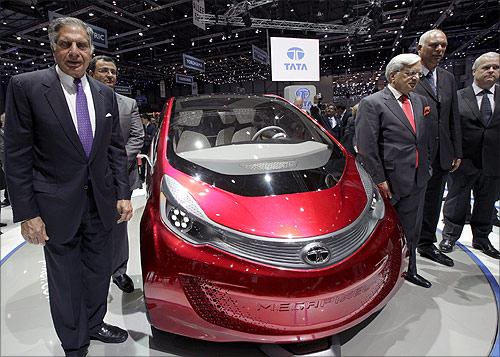 Tata Motors' Chairman Ratan Tata (L) poses in front of the Megapixel model car during the first media day of the Geneva Auto Show at the Palexpo in Gene