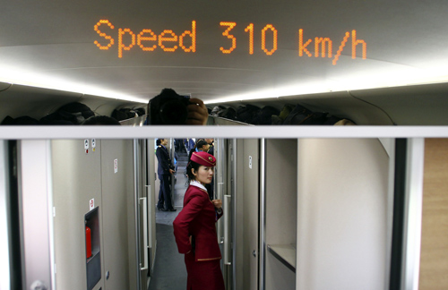 An attendant stands inside a high-speed train during an organized experience trip from Beijing to Zhengzhou, as part of a new rail line.