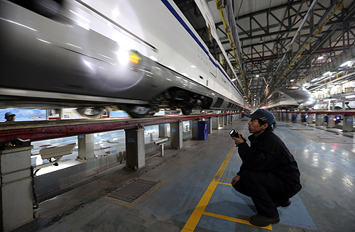 An employee uses a flashlight to inspect a CRH380 (China Railway High-speed) Harmony bullet train at a high-speed train maintenance base in Wuhan, Hubei province.