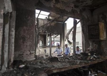 Private security guards stand behind a damaged reception block of Maruti Suzuki's plant in Manesar, located in Har