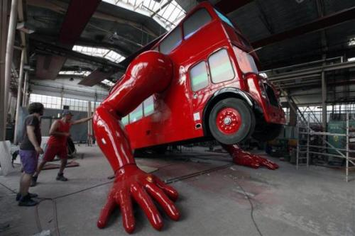 Workers check the function of the hydraulic arms of a London bus that is being transformed into a robotic sculpture.