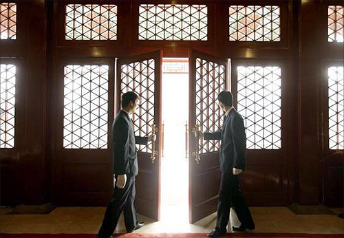 Waiters open a Chinese traditional red door inside a luxurious furniture museum in Beijing.