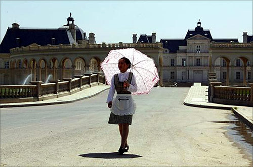 A waitress carrying an umbrella walks down the driveway to Chateau Laffitte Hotel, an imitation of the 1650 Chateau Maisons-Laffitte by French architect Francois Mansart, located on the outskirts of Beijing.
