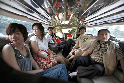 Family members of a couple getting married sit inside a Hammer Limousine on the drive to the wedding reception in Shanghai.