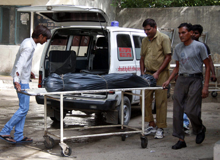 Hospital staff move the covered body of