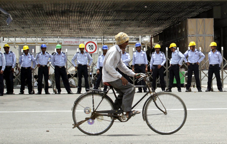 A man rides his bicycle past private security guards standing outside the main entrance to the Maruti Suzuki India.