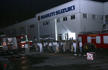 Police and firefighters are seen at the Maruti Suzuki's plant after a clash in Manesar.