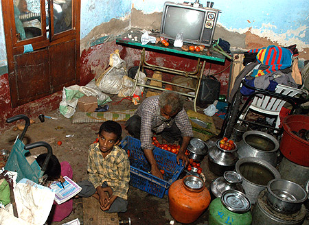 Vasim Khan (L), a 10-year-old polio victim, sits with his father Abdul Rasheed in their house in the southern Indian city of Bangalore.