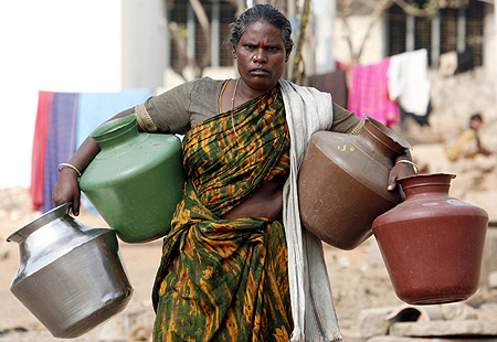 A woman walks to a tap to collect water on the outskirts of Bengaluru..
