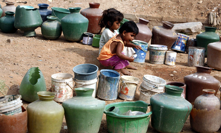 Children sit beside empty plastic cans used to collect water from a tap on the outskirts of Bangalore.