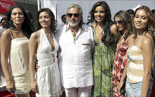 Chairman of United Breweries group Vijay Mallya (C) poses with models featured in Kingfisher's new Swimsuit Special 2007 calendar at a function in Mumbai.