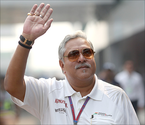 Force India team principal Vijay Mallya waves in the paddock during the third practice session of the Indian F1 Grand Prix at the Buddh International Circuit in Greater Noida, on the outskirts of New Delhi, October 27, 2012.
