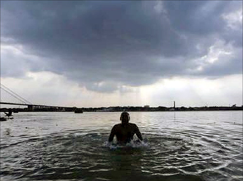 A devotee takes a dip against the backdrop of rain clouds in the river Ganga in Kolkata.