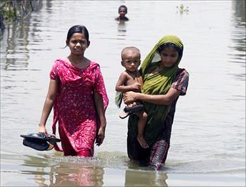 Women move through a flooded road.