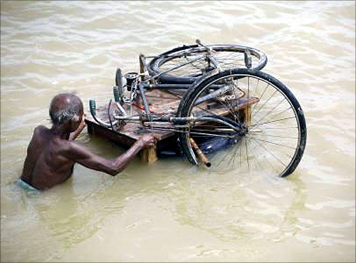 A man transports his bicycle through a flood-hit area of Darbhanga district, about 200 km north from Patna.
