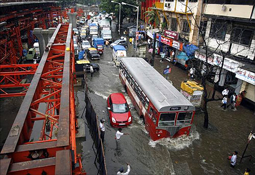 Floodwaters bog down traffic beside a bridge under construction after heavy rains swamped Mumbai.