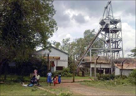 Schoolchildren play in front of an abandoned shaft at Kolar Gold Fields, located