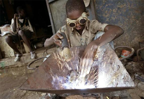 An Ivorian child welds in a wrought iron workshop in Abidjan, Ivory Coast.