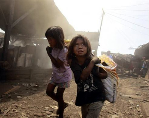 Girls carry sacks in a charcoal factory at a slum in Manila, Philippines.