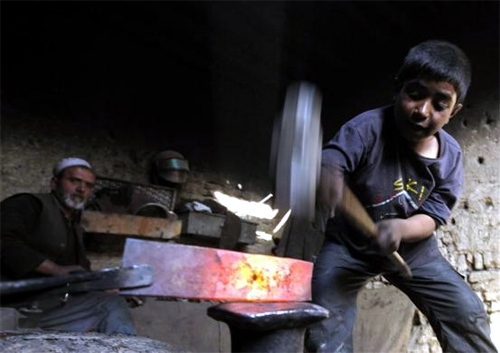 Afghan boy Abdul Wahab works in a blacksmith's shop in Kabul, Afghanistan.