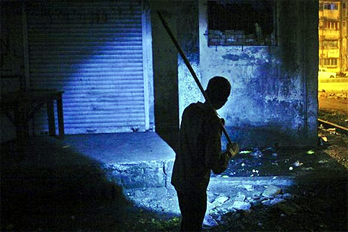 Waseem Sheikh, 12, holding an improvised stick searches for rats with the help of a torch outside a residential complex in Mumbai.