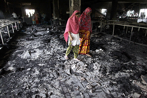 Workers visit a burnt garment factory after a fire which killed more than a hundred people in Savar.