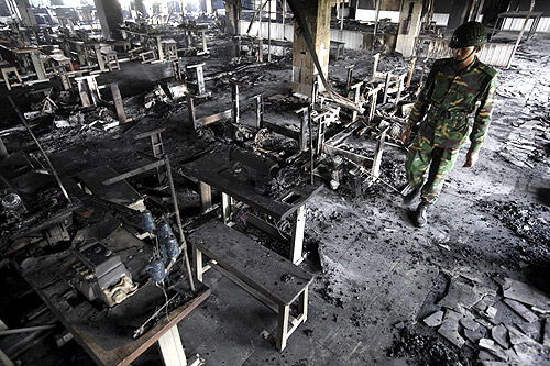 An army personnel inspects the burnt machineries of a garment factory after a devastating fire in Savar.