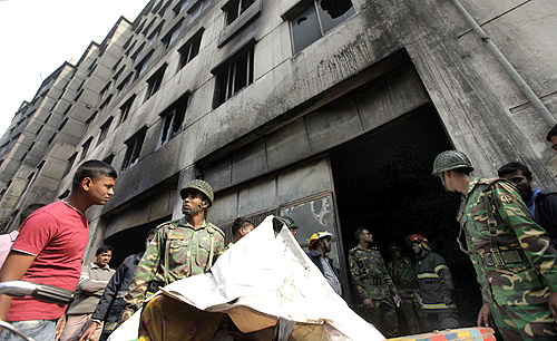 Army personnel load the body of a dead garment worker onto a rickshaw van after a devastating fire in a garment factory in Savar.