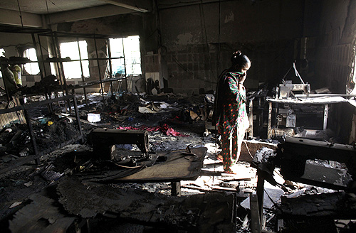 A worker visits a burnt garment factory after a fire which killed more than a hundred people in Savar.