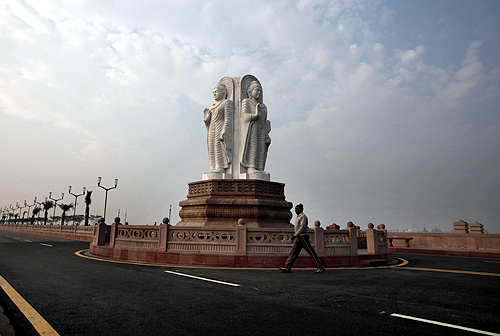 man walks in front of Buddha statues outside the Ambedkar memorial park in Lucknow.