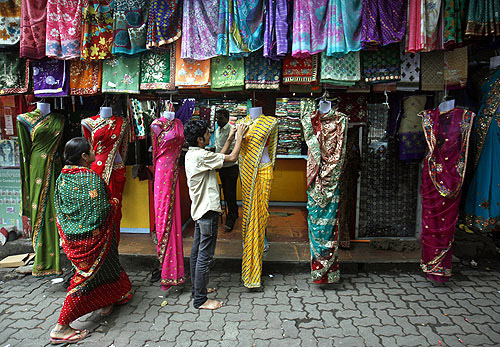 worker arranges sarees, a traditional cloth used for women's clothing outside a shop in Mumbai.