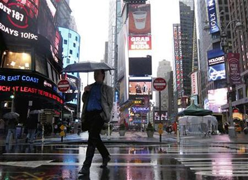 A man walks through Times Square as a massive rain storm drenched New York.