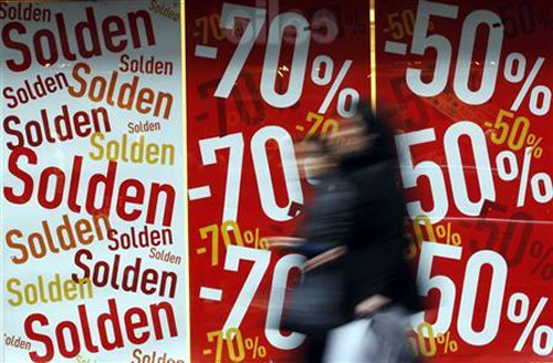 Two women walk past a clothing store on the first day of the winter sales in Brussels.