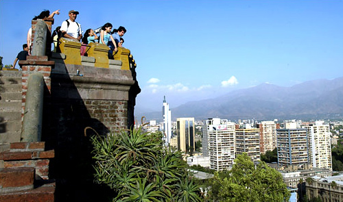 Tourists take in the view of the Andes Mountains from Santa Lucia Hill in downtown Santiago.