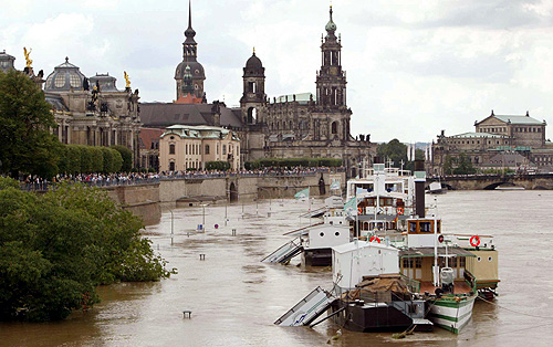 Boats are sen floating above the piers on a flooded street in front of the historic skyline of Dresden, along the banks of the river Elbe.