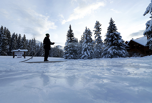 A hotel employee at Baker Creek Lodge  in Banff National Park sprays water down as he makes a ice skating rink near Lake Louise,  Alberta.