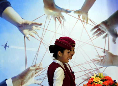 Flight attendants from China Southern Airlines stand inside a booth on the first day of the China International Aviation & Aerospace Exhibition in the southern Chinese city of Zhuhai.