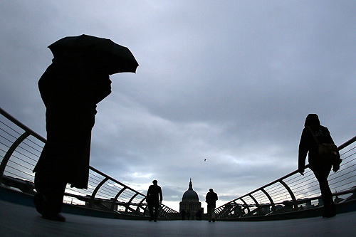Commuters cross the Millenium Bridge during a rainy morning, towards the financial district the City of London.