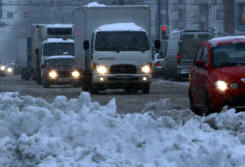 Vehicles drive during a heavy snowfall in Moscow.