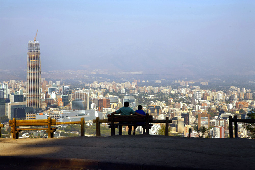 A man (L) sits with his son while enjoying the view of the Andes Mountains Range at the San Cristobal Hill in Santiago de Chile.