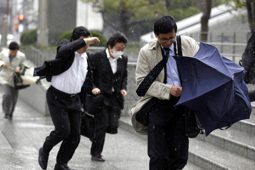 People brave the strong wind and rain in Tokyo April 3, 2012. Strong winds which hit Japan.