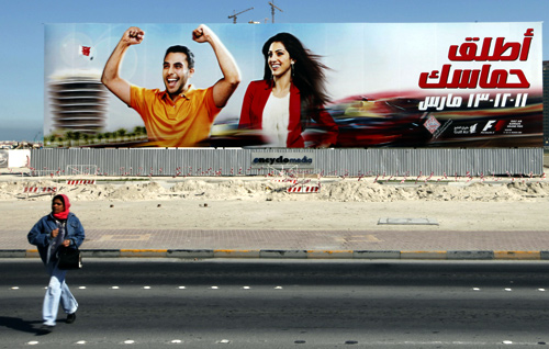 A woman walks in front of an advertisement for the Bahrain Formula One Grand Prix in Manama.