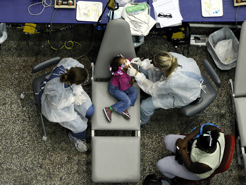 Kamora Cyprian, 2, has a dental exam at the Care Harbor/LA free clinic in Los Angeles.
