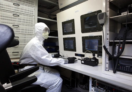 A military personnel, dressed in protective suit, monitors nuclear radiation in a Taiwan-made nuclear bio-chemical detection vehicle during a safety drill near a nuclear power plant in Shihmen, New Taipei City.