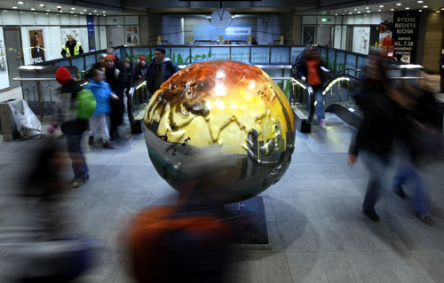 People walk past a globe as they leave a metro station in Copenhagen.