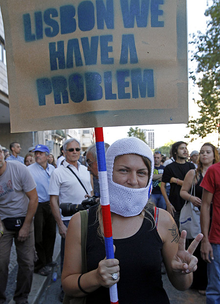 A woman holds a banner saying during a march against austerity in Lisbon.